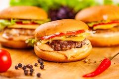 3 мини бургера с котлетами, томатами и сыром говядины на деревянной доске стоковое фото
