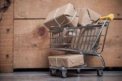 Мини вагонетка вполне пакетов для того чтобы послать дальше деревянное backgr стоковые фото