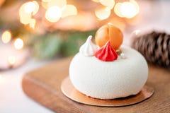 Мини десерт печенья мусса покрытый с белым велюром на предпосылке bokeh ламп гирлянды Современный европейский торт французско стоковые фотографии rf