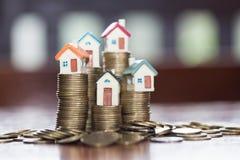 Мини дом на стоге монеток, деньгах и доме, недвижимости инвестирует стоковое фото
