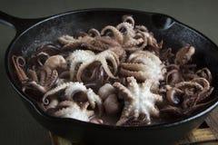 Мини осьминог в процессе жарки на лотке литого железа Стоковые Изображения RF