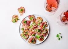 Мини открытые сандвичи с serrano jamon на белой плите и розовом вине стоковая фотография