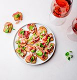 Мини открытые сандвичи с serrano jamon на белой плите и розовом вине стоковое изображение
