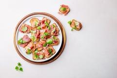 Мини открытые сандвичи с serrano jamon на белой плите стоковое изображение rf