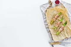 Мини спаржа в беконе на деревянной прерывая доске Белая предпосылка, взгляд сверху, космос для текста стоковые изображения rf