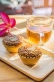 Мини торт и чай миндалины на деревянном столе Селективный фокус Стоковое Изображение