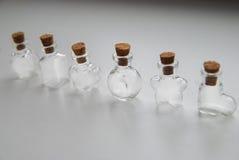 Мини формы стеклянных бутылок различные с затвором пробочки на белой предпосылке Стоковые Фотографии RF