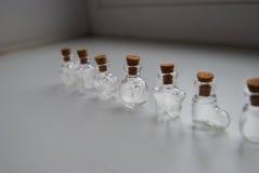 Мини формы стеклянных бутылок различные с затвором пробочки на белой предпосылке Стоковое Изображение RF