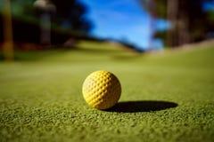 Мини шарик желтого цвета гольфа на зеленой траве на заходе солнца Стоковые Изображения RF