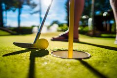 Мини шарик желтого цвета гольфа с летучей мышью около отверстия на заходе солнца Стоковое Фото