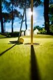 Мини шарик желтого цвета гольфа с летучей мышью около отверстия на заходе солнца Стоковая Фотография