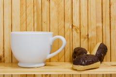 Мини Eclairs с чашкой чаю Стоковые Изображения