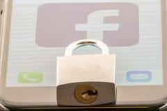 МИННЕАПОЛИС, МИНЕСОТА/США - 10-ОЕ ИЮНЯ 2019: Замок на iPhone с хранителем экрана значка Facebook - вопросы безопасностью и уедине стоковая фотография rf