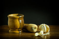 Миномет и пестик с чесноком на деревянном столе Стоковая Фотография RF