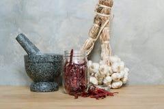 Миномет чеснока перца Chili на деревянном столе Стоковое Изображение RF