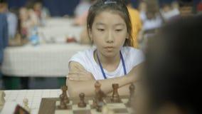 Минск, Беларусь - 22-ое июня 2018 Портрет азиатской девушки играя шахмат сток-видео