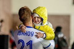 МИНСК, БЕЛАРУСЬ - 31-ОЕ МАРТА 2018: Футболист с ребенк празднует выигрыш после белорусского футбольного матча премьер-лиги стоковое фото rf