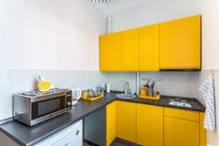 МИНСК, БЕЛАРУСЬ - ЯНВАРЬ 2019: Интерьер современной кухни в квартире просторной квартиры плоской в минималистичном стиле с желтым стоковое изображение