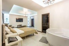 МИНСК, БЕЛАРУСЬ - январь 2019: квартиры внутренней просторной квартиры залы luxure плоские с софой и креслами ТВ стоковая фотография rf