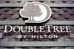 Минск, Беларусь - 17-ое июня 2017: Логотип на фасаде гостиницы строя двойное дерево Hilton Hotel Минском Стоковые Изображения RF