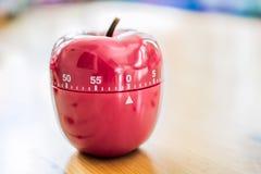 0 минут/1 час - таймер яичка кухни в форме Яблока на деревянном столе Стоковое Фото