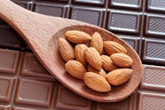 Миндалины в деревянной ложке на предпосылке шоколада Стоковые Изображения RF