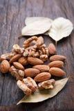 Миндалины и грецкие орехи на деревянной предпосылке Селективный фокус Стоковое Изображение RF