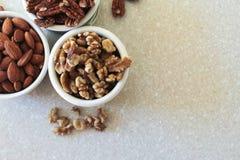 Миндалины, пеканы, грецкие орехи в контейнерах, расположили с верхнего Lef Стоковое Фото