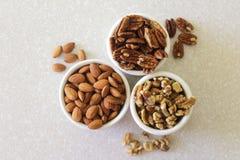 Миндалины, пеканы, и грецкие орехи в контейнерах на Countertop кухни Стоковые Изображения RF