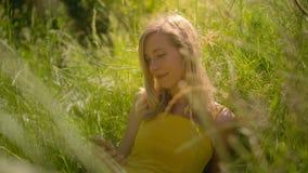 Мирная женщина в солнечном outdoors используя умный телефон видеоматериал