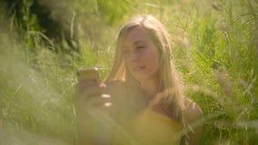 Мирная женщина ослабляя в красивом солнечном outdoors смотря умный телефон сток-видео
