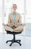 Мирная шикарная коммерсантка сидя в положении лотоса на вращающееся кресло Стоковое Изображение