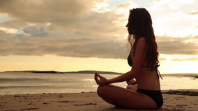 Мирное брюнет размышляя на песке на заходе солнца сток-видео