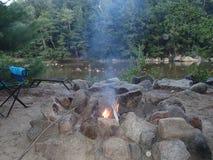 Мирный лагерный костер, который нужно ослабить и размотать около пропуская реки Стоковая Фотография RF