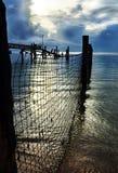 Мирный день кончает солнце устанавливая над рыболовными сетями причалом & морем Стоковое Изображение RF