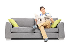 Мирный молодой человек читая усаженные новости на софе Стоковые Изображения