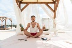 Мирный парень при борода ослабляя на пляже на каникулах Стоковое Фото