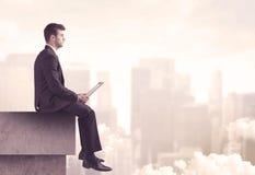 Мирный парень продаж сидя на верхней части крыши Стоковые Изображения