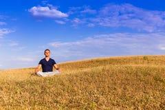 Мирный пейзаж человека размышляя в положении лотоса Стоковое Фото