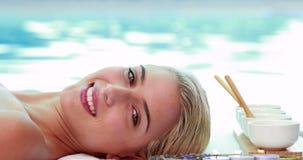 Мирный усмехаясь белокурый лежать на poolside таблицы массажа видеоматериал