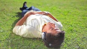 Мирный человек брюнет лежа на траве пока слушающ к музыке сток-видео