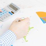 Мир дела и свои символы - бизнесмен занятый делающ некоторые вычисления на столе Стоковое фото RF