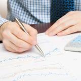 Мир дела и свои символы - бизнесмен занятый с вычислениями над некоторыми финансовыми данными Стоковые Изображения RF