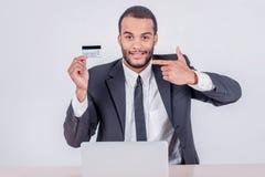 мир компенсации карты интернета глобуса кредита принципиальной схемы карточки банка Успешный африканский бизнесмен сидя на Ла Стоковые Изображения