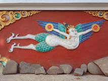 Мифологический тибетский бог Garuda с белым телом и голубые крыла на бургундской стене тибетского stupa, Китая Стоковые Фотографии RF