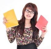 Милая азиатская девушка держа 2 цвета книг, красных и желтых Стоковая Фотография RF