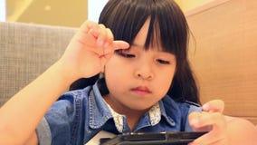 Милая азиатская девушка играя умный телефон видеоматериал