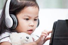 Милая азиатская девушка маленького ребенка в наушниках использует таблетку Стоковые Фото