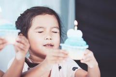 Милая азиатская девушка маленького ребенка держа пирожное дня рождения Стоковое фото RF