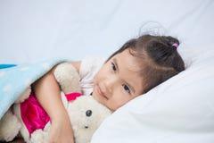 Милая азиатская девушка маленького ребенка обнимая ее плюшевый медвежонка Стоковые Изображения